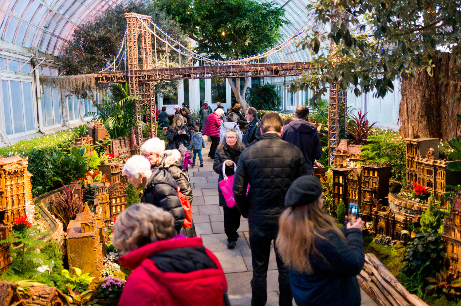 Patrons watch the trains go by in the Holiday Train Show at the New York Botanical Garden.