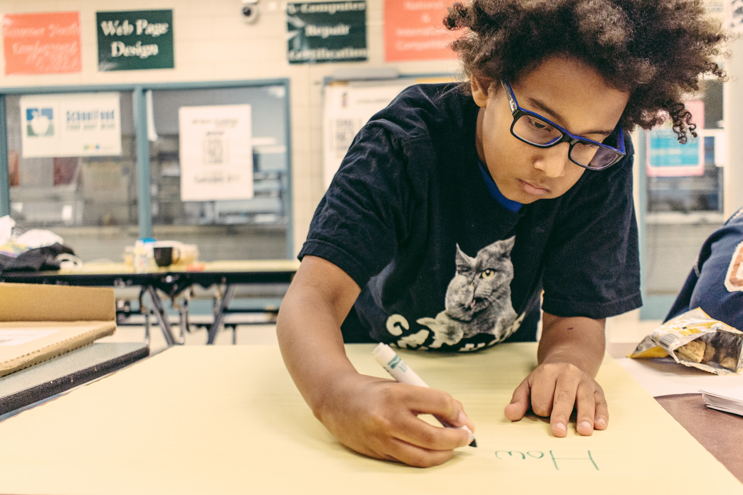 Otis Samb, 11, writes out information for 'Pollinators vs. People,' a game he and three classmates created for IN-Tech Academy's first hack-athon. It is part of the education department's CS4All Hack League, a citywide coding competition.
