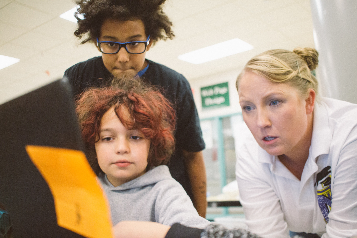 Otis Samb, 11, and Max Rossiter, 11, look on as computer science teacher Beth Colavito  evaluates their game 'Pollinators vs. People.'