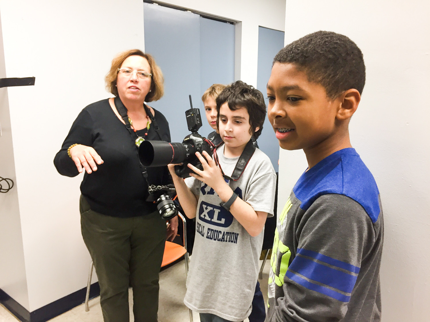 Eileen McNamee, a volunteer with the Bronx Photo Collective, gives students tips on taking professional quality photos. McNamee, along with fellow volunteer Walter Pofeldt, are documenting the meeting between the students and senior citizens as part of an inter-generational pilot program.