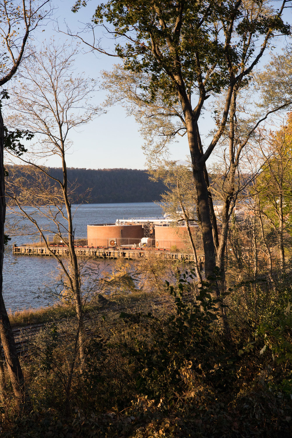 The Westchester County wastewater treatment plant that borders Riverdale and train tracks are seen along the riverfront in an area blocked off from public access.
