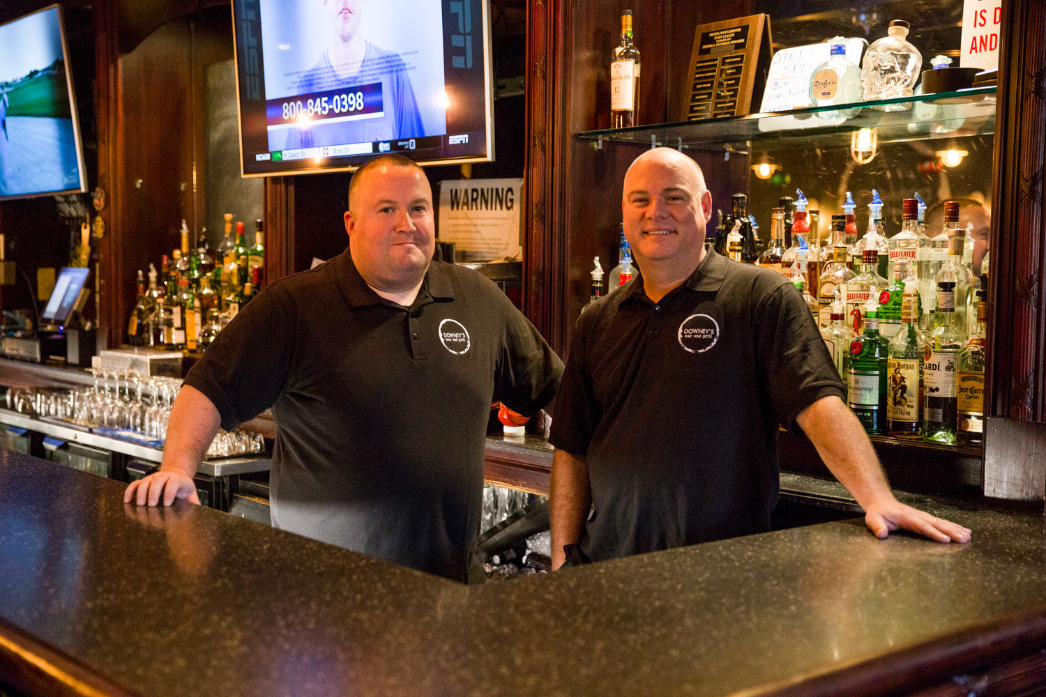 Owners Brian Downey and Bobby Cook stand behind the bar at Downey's Bar and Grill. The two opened Downey's Bar and Grill at the end of October.