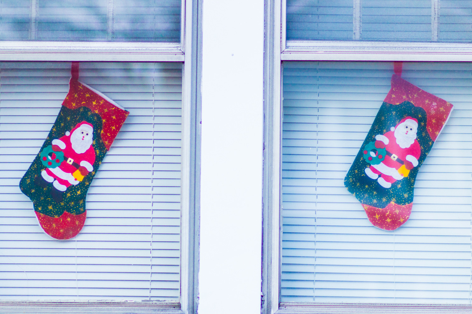 Christmas stockings hang in the windows of a home.