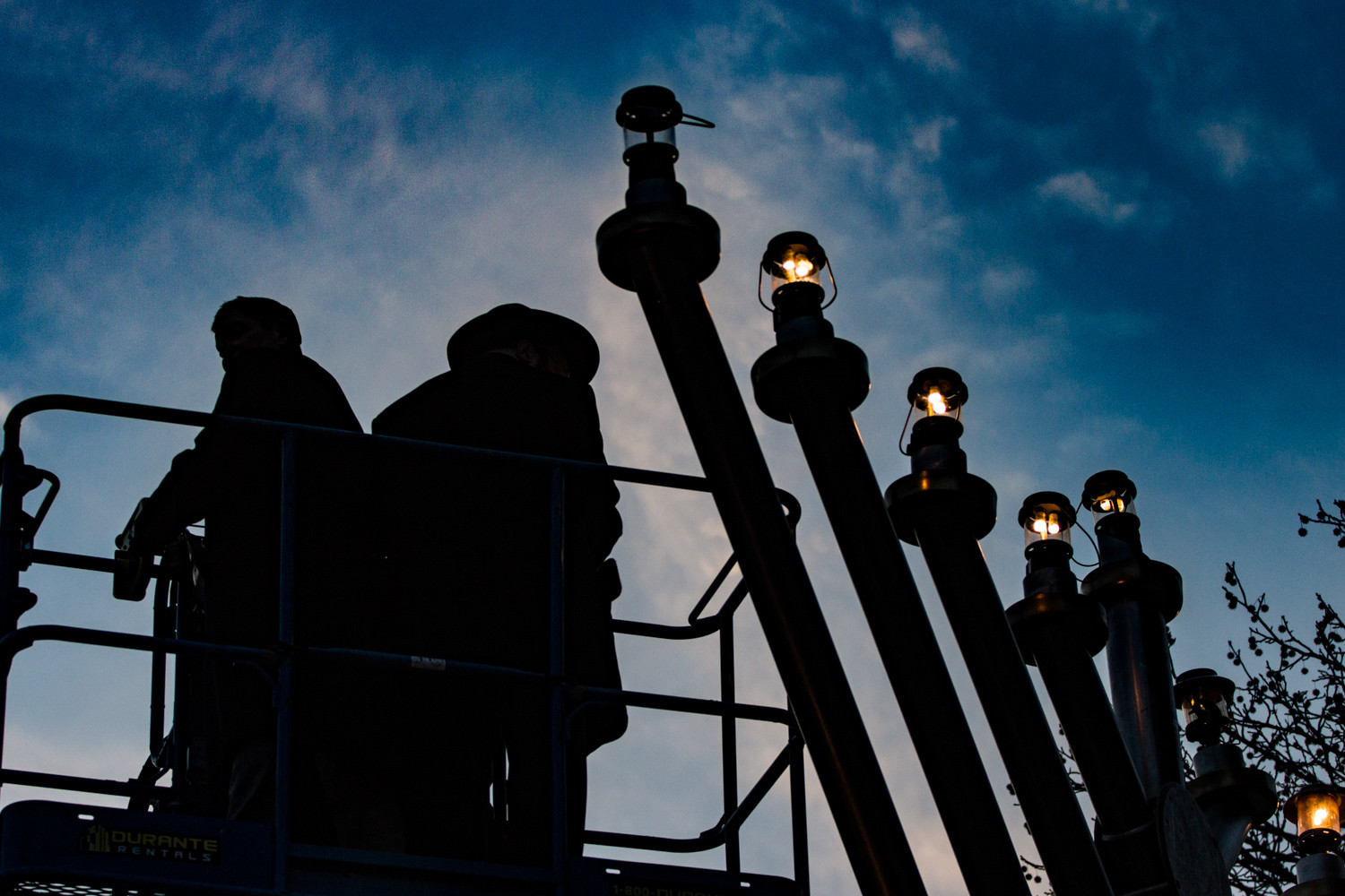 The silhouettes of state Sen. Jeffrey Klein, left, and Rabbi Levi Shemtov stand atop a hydraulic platform as they light the 23-foot menorah near the Riverdale Monument last Sunday to celebrate Hanukkah.