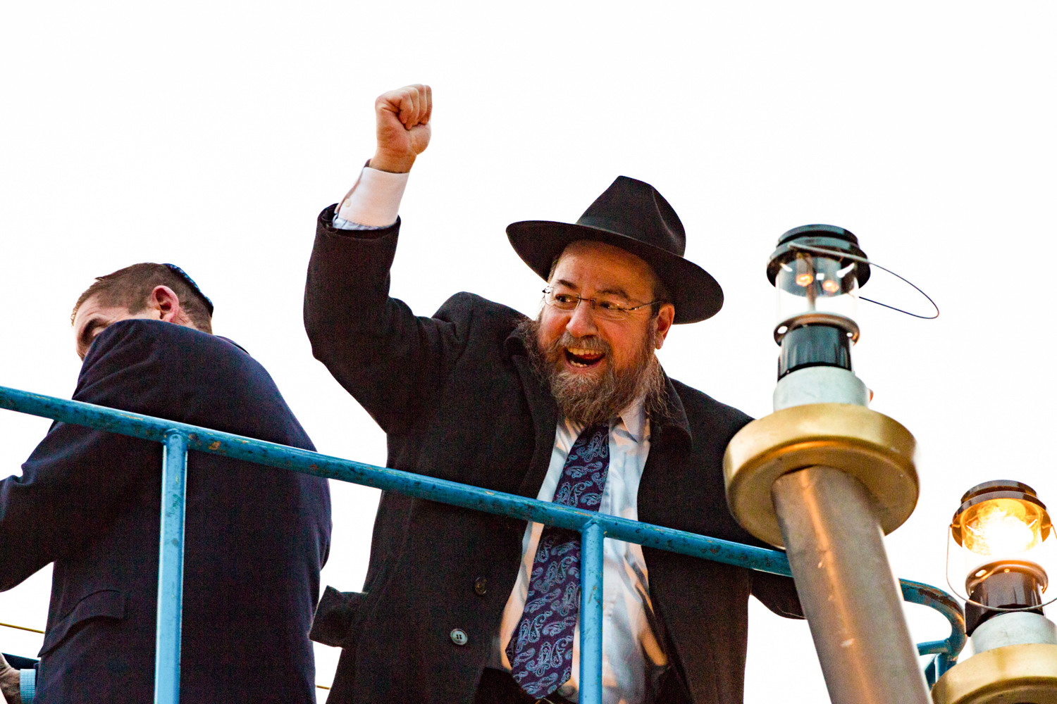 Rabbi Levi Shemtov celebrates with a raised fist to the crowd below after successfully lighting the sixth branch of the menorah on Sunday at the Riverdale Monument.