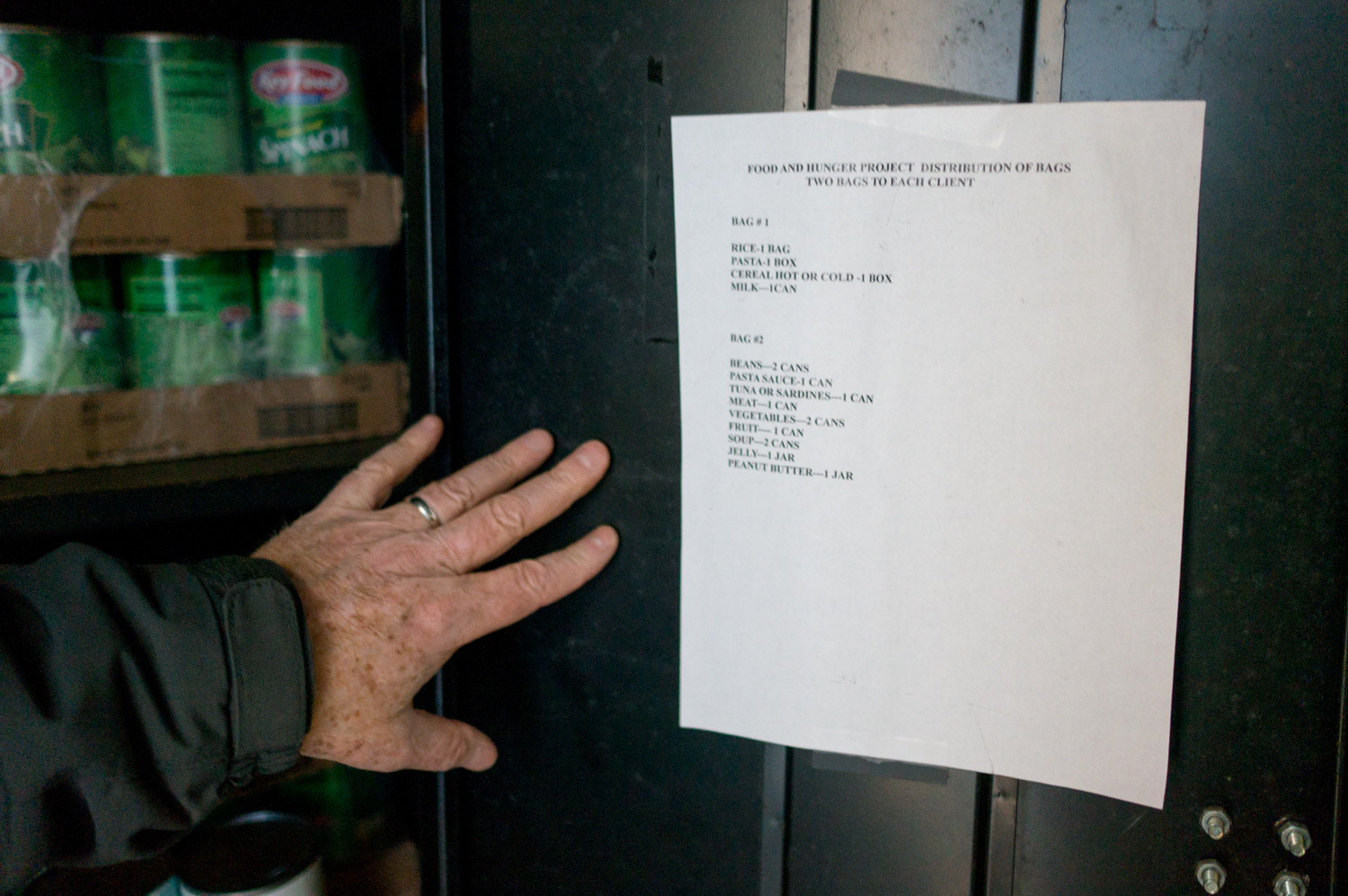 A master list pasted on the door of a cabinet inside the shipping container shows how each bag should be packed. The Kingsbridge Riverdale Marble Hill Food & Hunger Project distributes two bags of groceries per person each week.