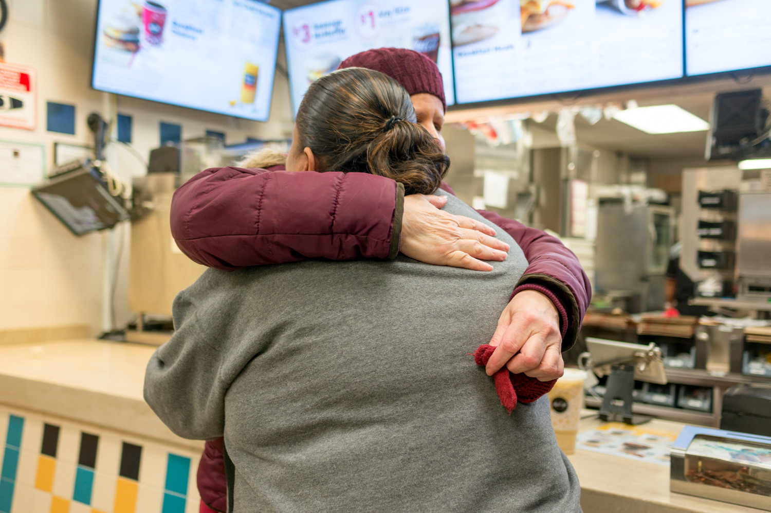 Maria Lugo hugs the store manager in the McDonald's at 5201 Broadway on Monday, its last day of operation. Lugo has been a customer there since moving to the neighborhood 10 years ago.