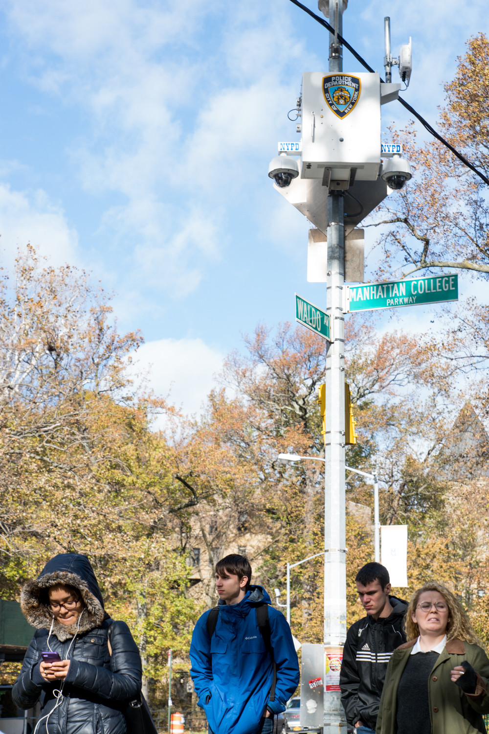 Pedestrians walk under New York Police Department security cameras at the intersection of Manhattan College Parkway and Waldo Avenue. The 50th Precinct wants to install more cameras in Marble Hill, where business owners and residents have said crime is a problem.