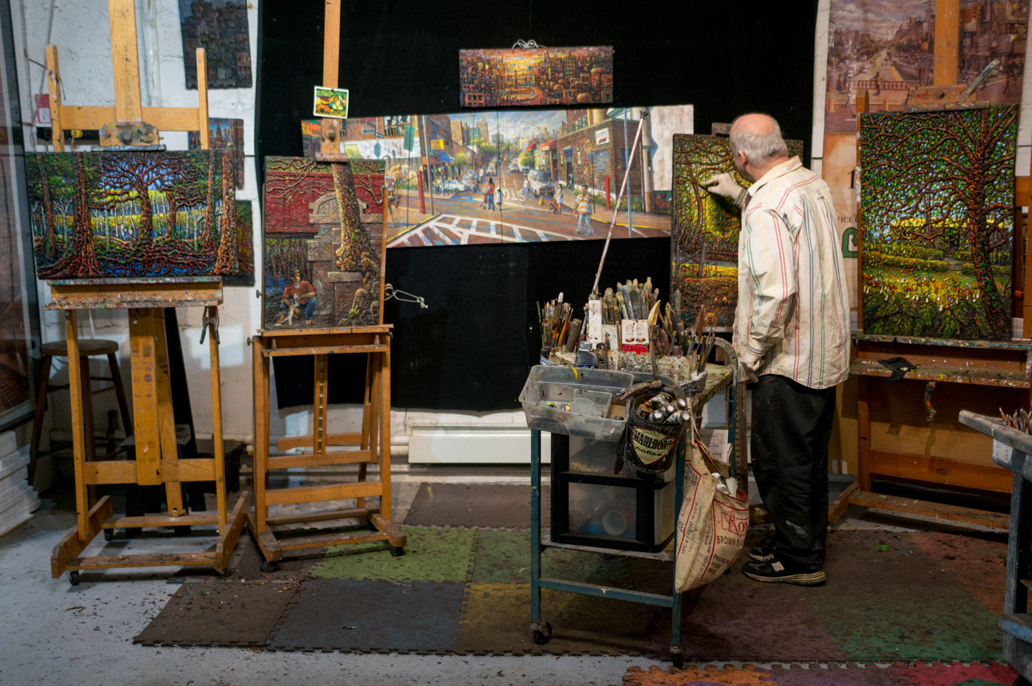 Daniel Hauben works on a painting in his studio. Hauben's paintings are often known for their texture in which figures rise off the canvas creating a three-dimensional effect.