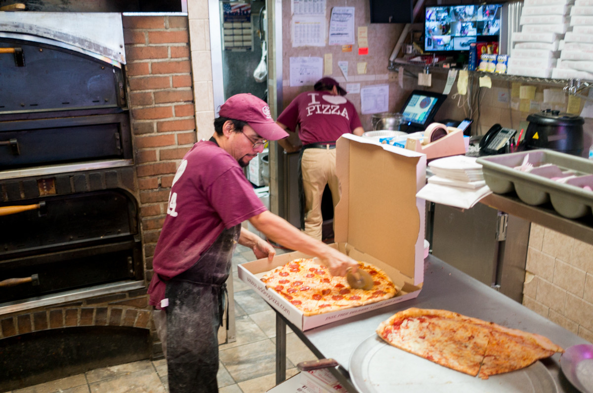 Cooks at Addeo's Riverdale Pizza prepare pies during winter storm Grayson, a bomb cyclone blanketing Riverdale. 'Snowstorms are some of the busiest days around,' said Laurence Addeo, the owner of Addeo's Riverdale Pizza.