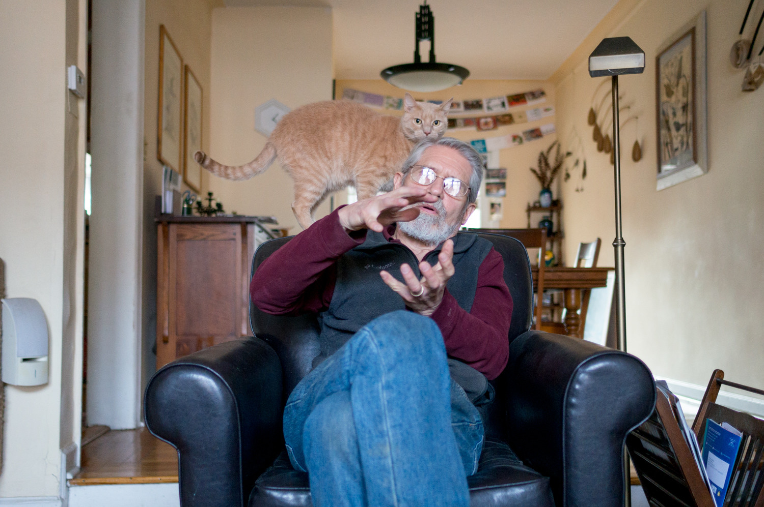 Ivan Braun shows approximately how big an urn for a cat would be while his 5-year-old cat Archie stands behind him. Braun is a professional woodturner who makes a variety of objects including bowls, vases and urns for cats.