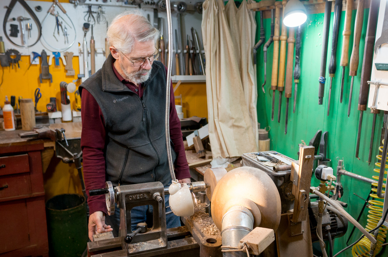 Ivan Braun prepares his lathe in the basement of his home. A lathe works by spinning a block of wood at a high speed while a woodturner applies a chisel to shape the wood. Braun is a professional woodturner who makes household objects that are more functional than ornate.