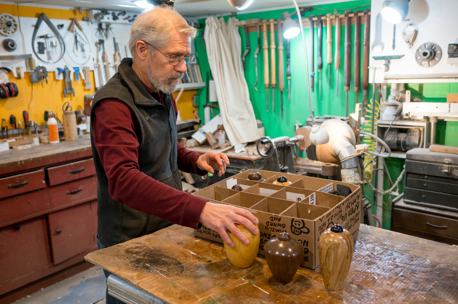 Ivan Braun places several urns designed for cats on the workbench in the basement of his home. Braun is a professional woodturner who, in addition the bowls and vases he's known for, also makes urns specifically for cats.