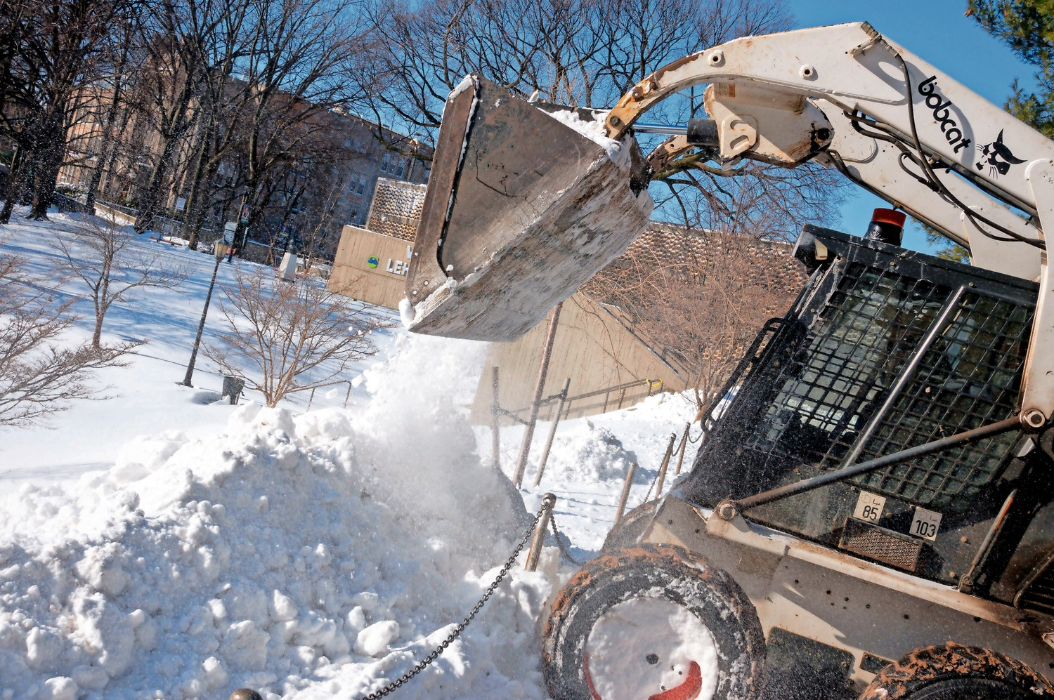Dennis Mosman dumps snow on a hill at Lehman College. The buildings and grounds staff at Lehman College put in extra hours to clear the snow in the aftermath of the bomb cyclone.