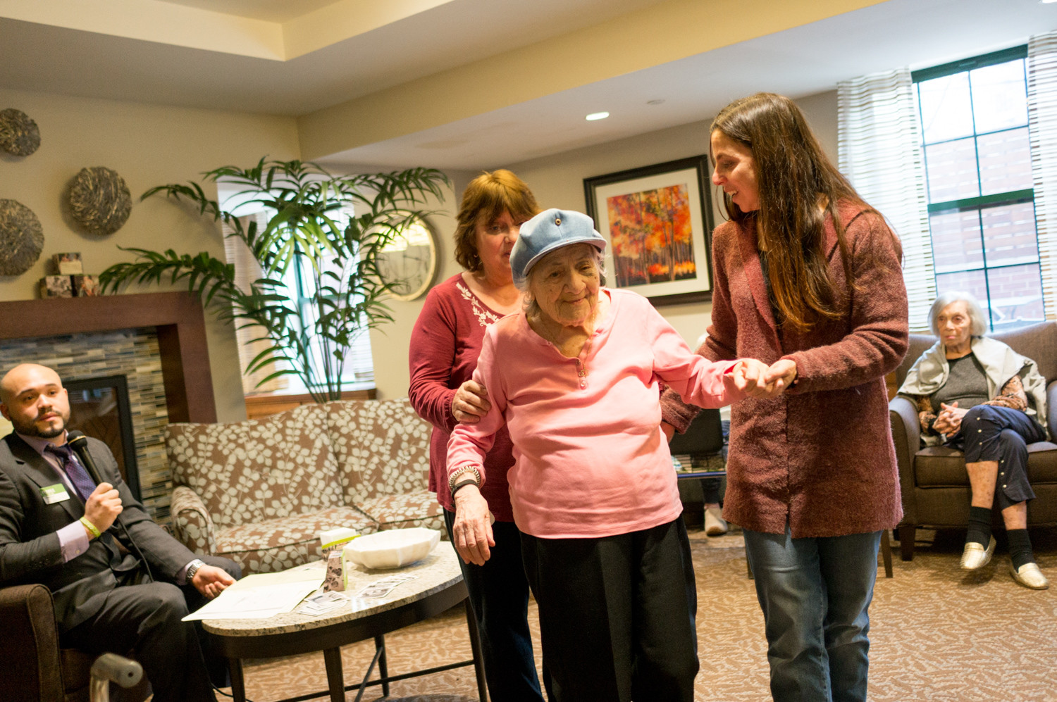 Ruth Abrams is helped to her seat by her daughter and granddaughter at Atria Riverdale after sharing a story about an influential teacher she had. During the event, Abrams' daughter, Barbara Confino, and granddaughter, Rebecca Confino, learned a story about Abrams' childhood she had never shared.