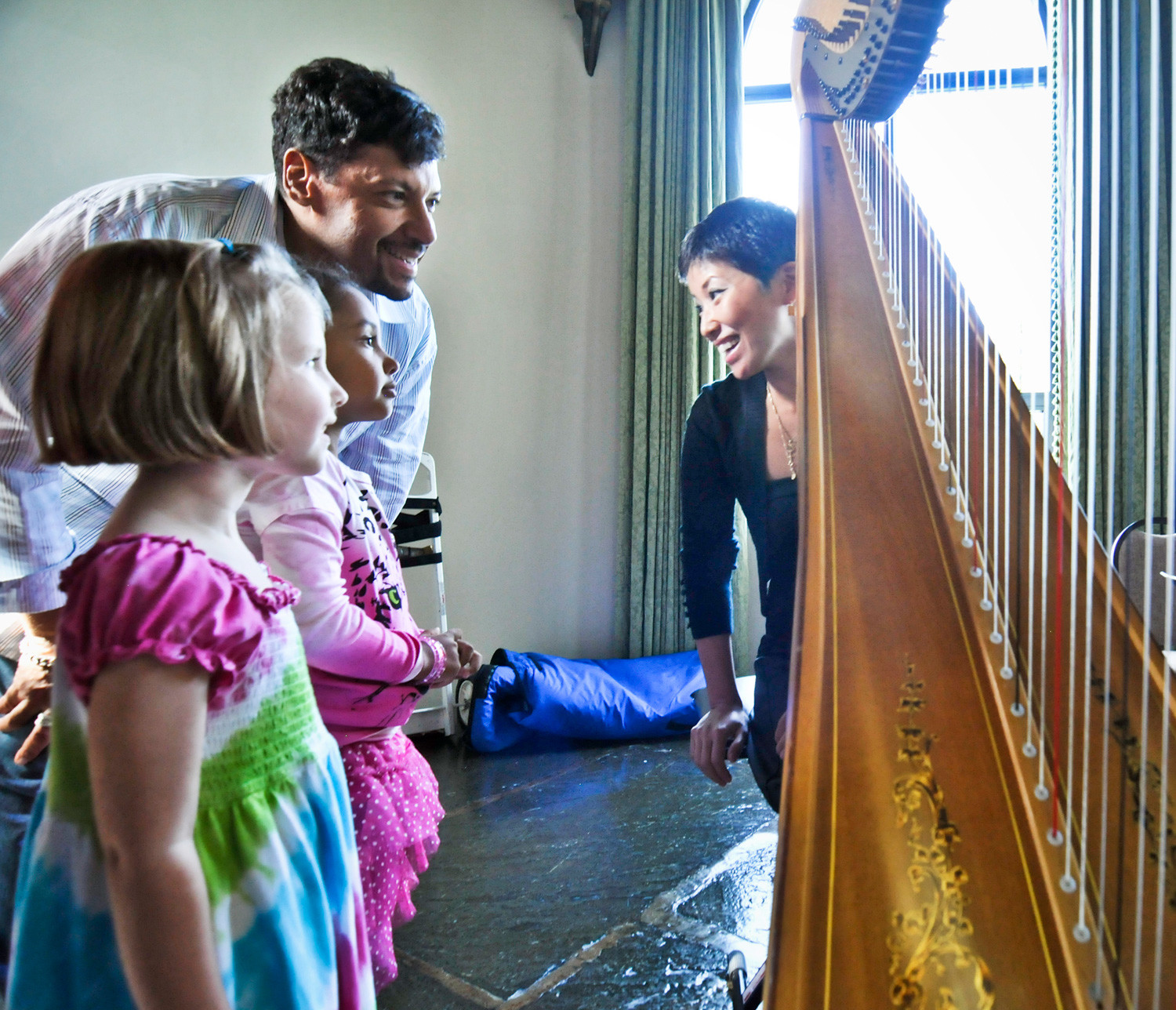 Harpist June Han interacts with children at a family concert The Sinfonietta of Riverdale held a few years ago. The classical music group is celebrating its 10th anniversary.