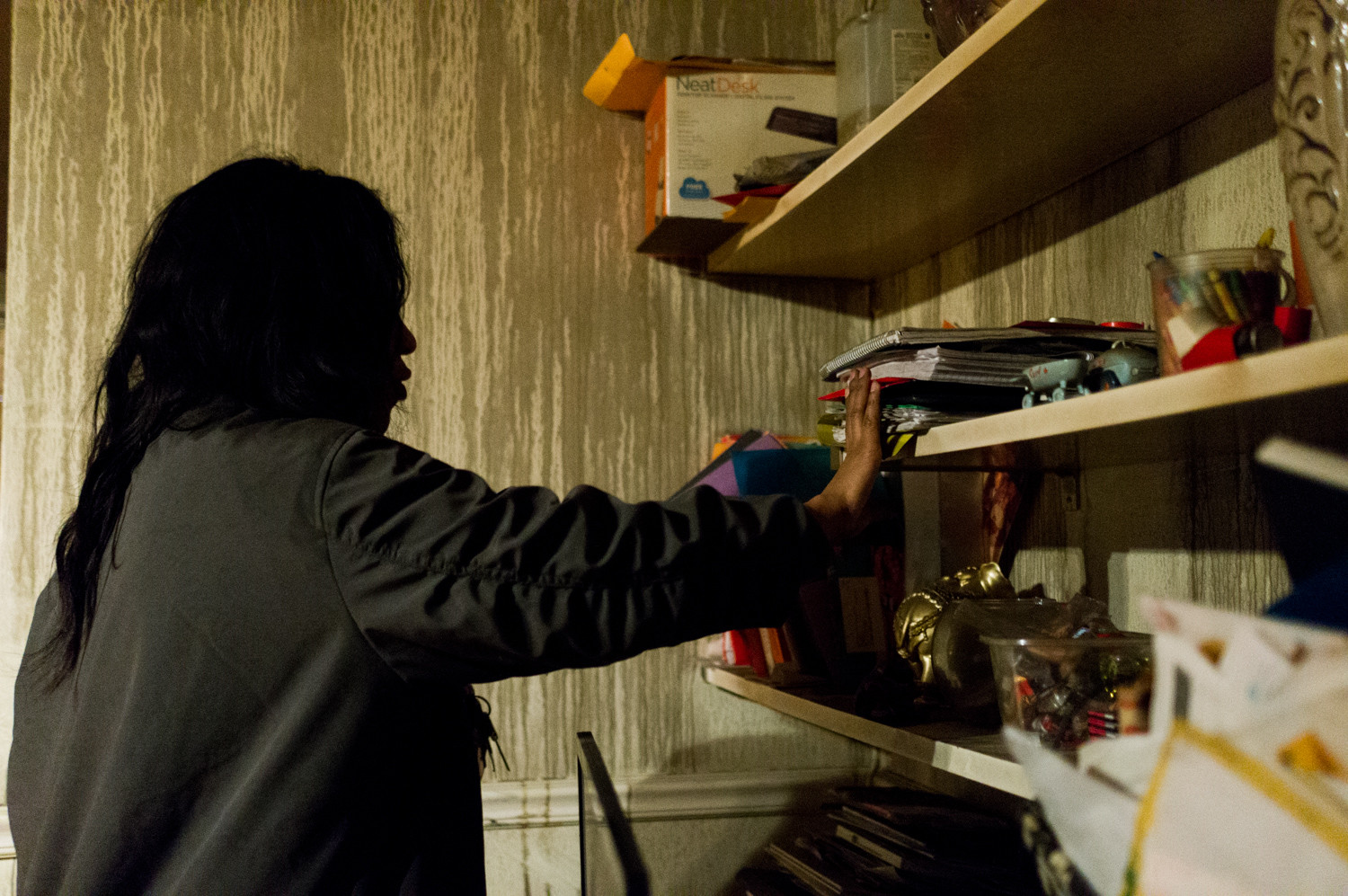 Ana Anderson looks through what was left behind in her 6035 Broadway apartment after a fire.