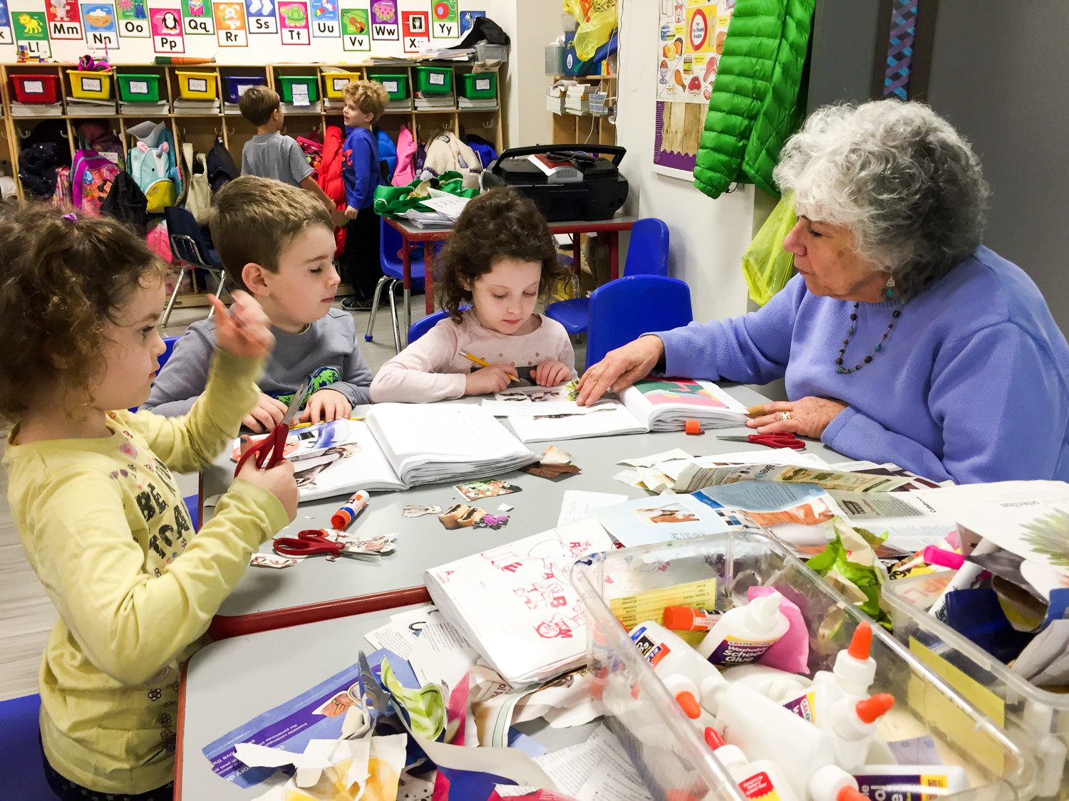 Dorit Niven, a kindergarten teacher at Kinneret Day School, helps her students, Lucy Mandl, left, Yuval Davis and Romy Marinacci, learn about the five senses — sight, smell, taste, touch and sound.