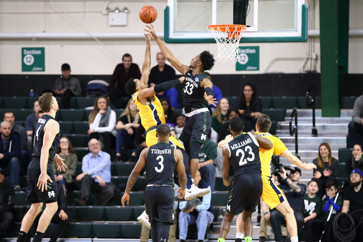 Manhattan's Pauly Paulicap (33) registers one of his six blocks, but it wasn't enough to lift Manhattan past Canisius last Friday.