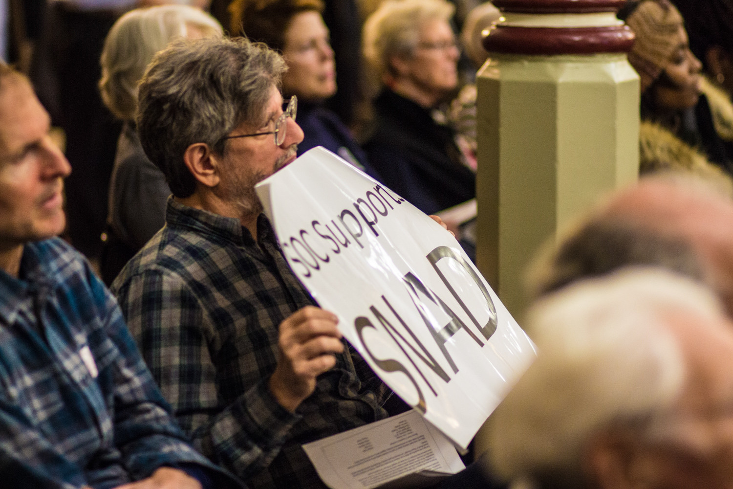 An attendee holds a sign reading, 'SOC supports SNAD.' Some residents of Skyview-on-the-Hudson have fiercely opposed plans to expand neighboring Hebrew Home at Riverdale, claiming it would undermine North Riverdale's status as a Special Natural Area District.