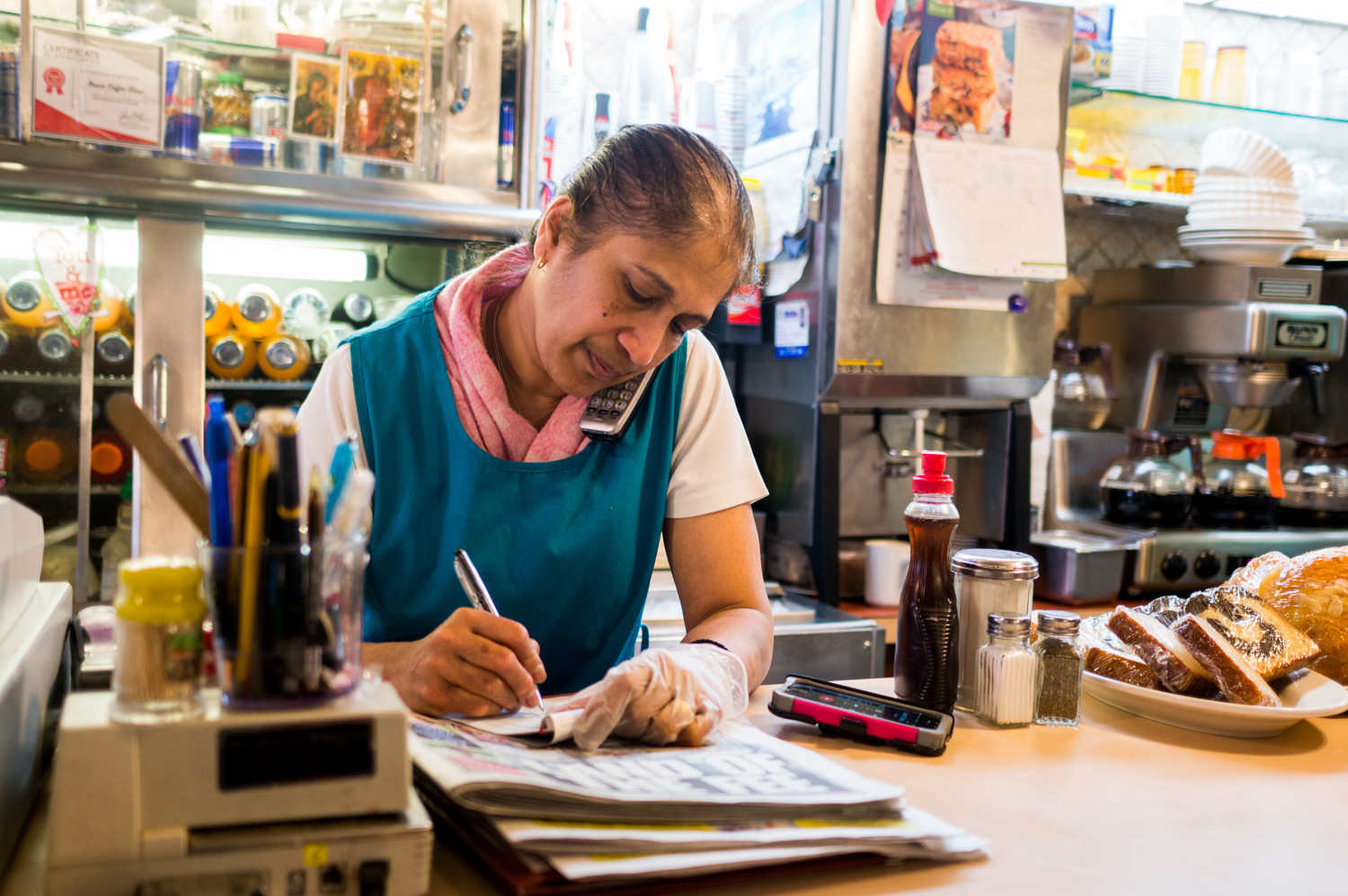 Ruth Tzanetatos, the owner of Noni's Coffee Shop on Riverdale Avenue, takes a customer's order over the phone. Her cook, Pedro Torres, is recovering at home from an injury, increasing the strain on Noni's remaining staff.