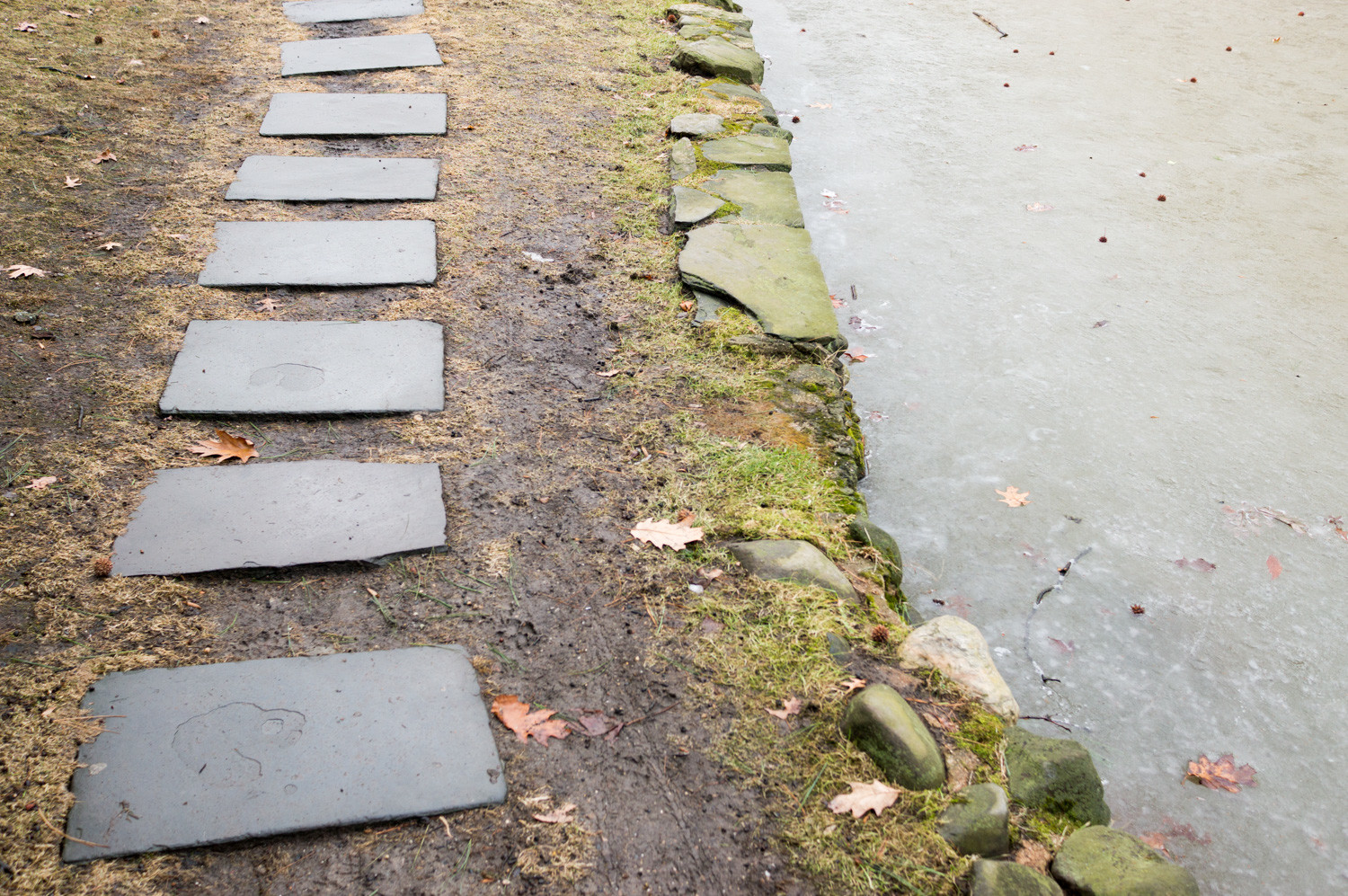 A stone path runs along the side of Indian Pond in Fieldston. A controversial plan to develop 1.3 acres of land overlooking the pond looks like it might be dead, as the property is up for sale.
