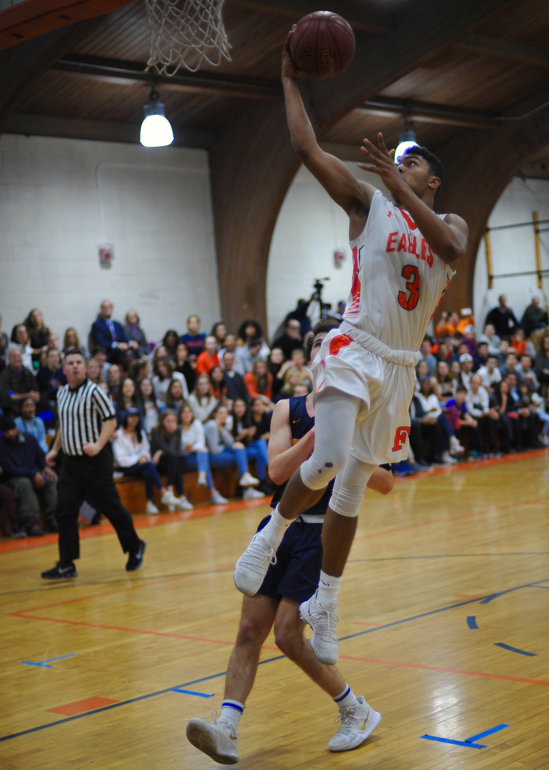 Fieldston's Jared Maharaj soars over a Trinity defender on his way to a 25-point day in the Eagles' victory last Friday.