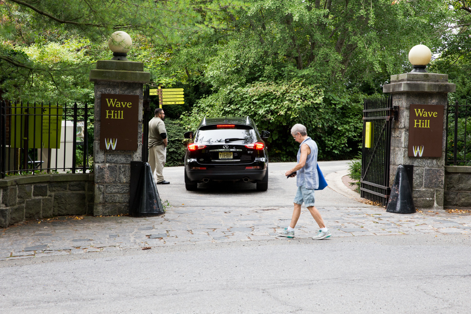 A pedestrian approaches Wave Hill's main entrance as a car pulls in during the summer months. Wave Hill is currently in the process of designing a pedestrian entrance south of its current entrance.