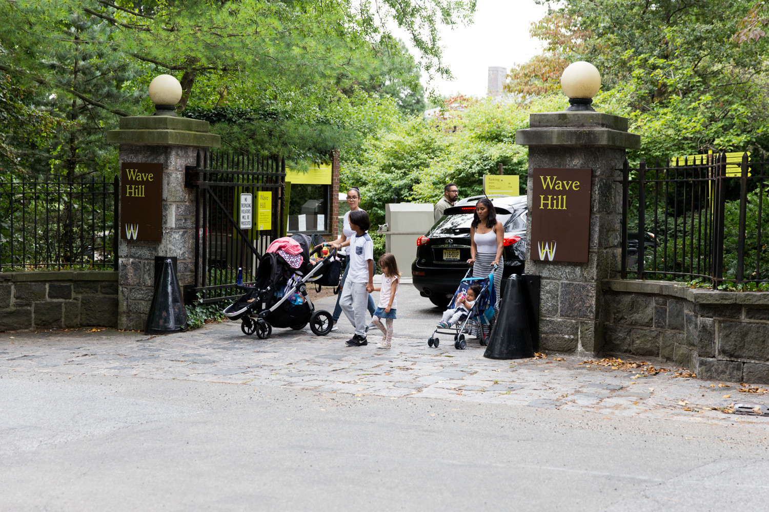 A family leaves Wave Hill as a car enters through the main gate last summer. The entrance, located at West 249th Street and Independence Avenue, will soon be restricted only to vehicles as a new pedestrian entrance is being designed for the south side of the garden.