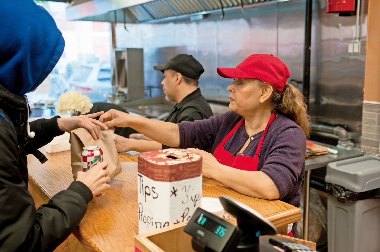 Maritza Hernandez, the owner of Amor Eterno, hands a sandwich to a customer. Specializing in tacos, Amor Eterno opened Jan. 13.
