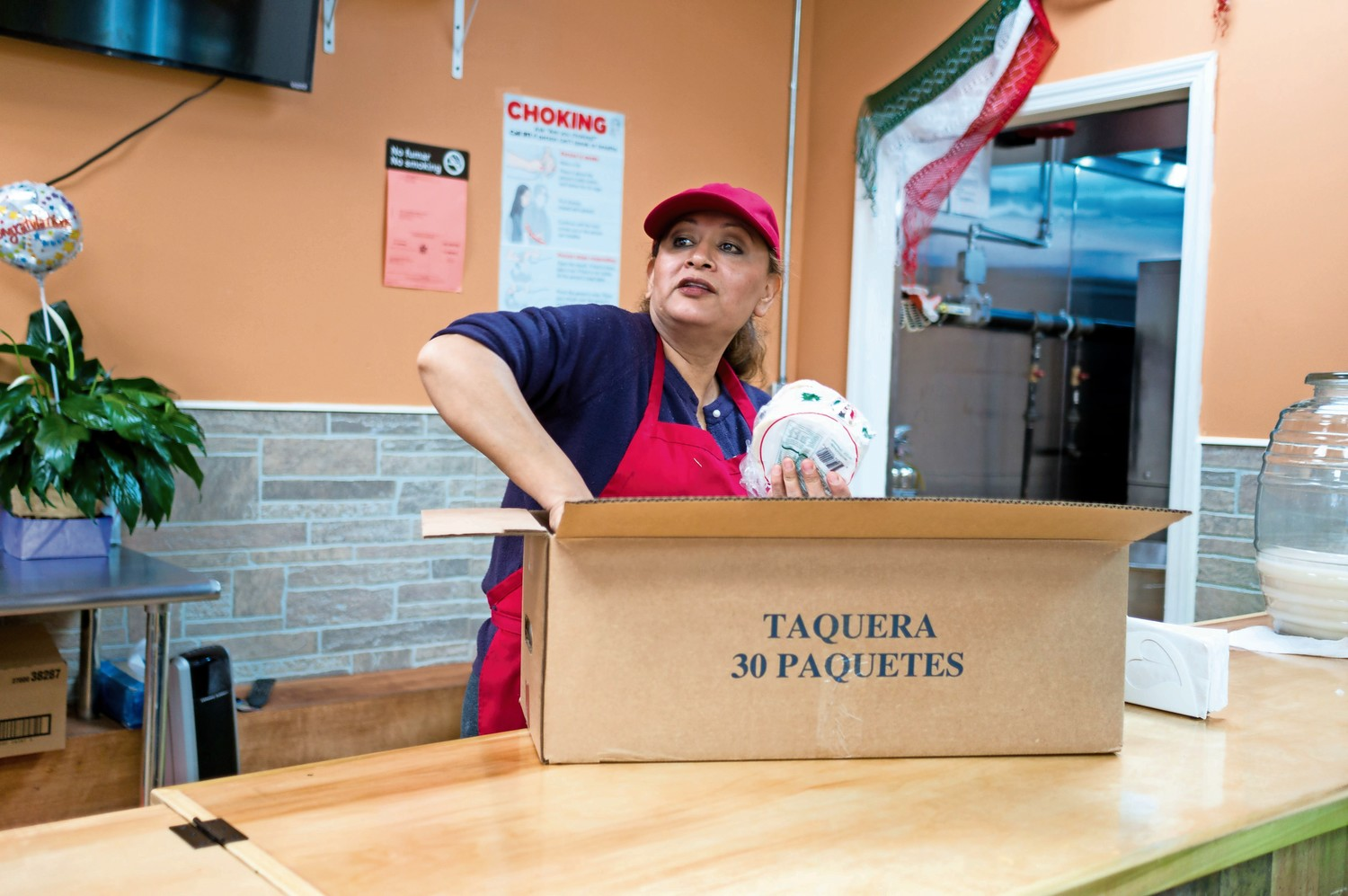 Maritza Hernandez, the owner of Amor Eterno, unloads a box of taco shells.