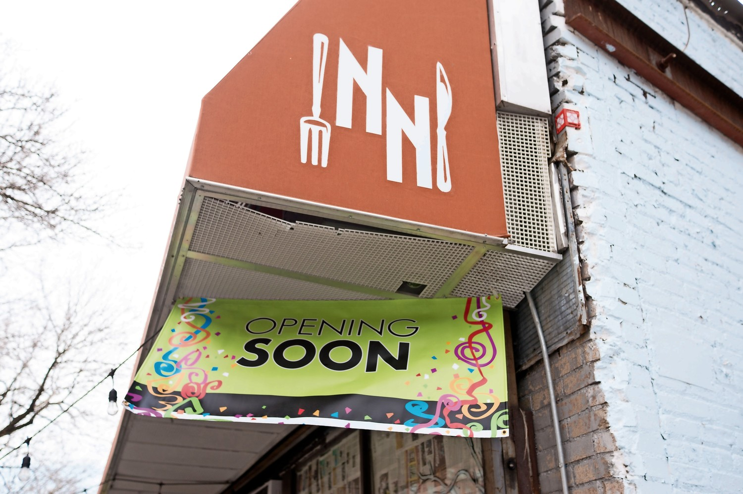 A 'coming soon' banner hangs under the awning of what was once Novelty Nachos. The restaurant will reopen with a new name under new management.