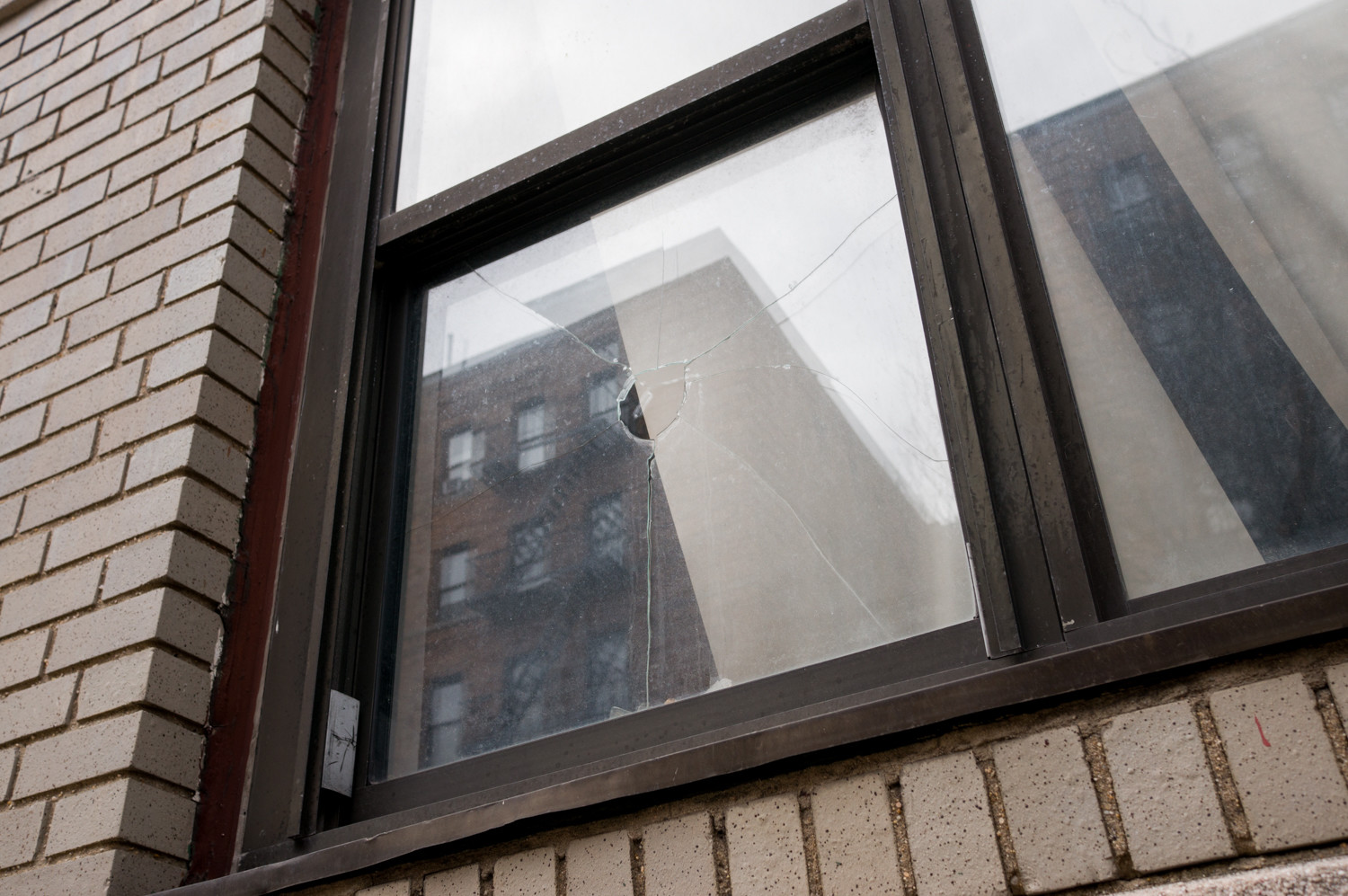 A ground-floor apartment window at 3045 Godwin Terrace has a hole in it.