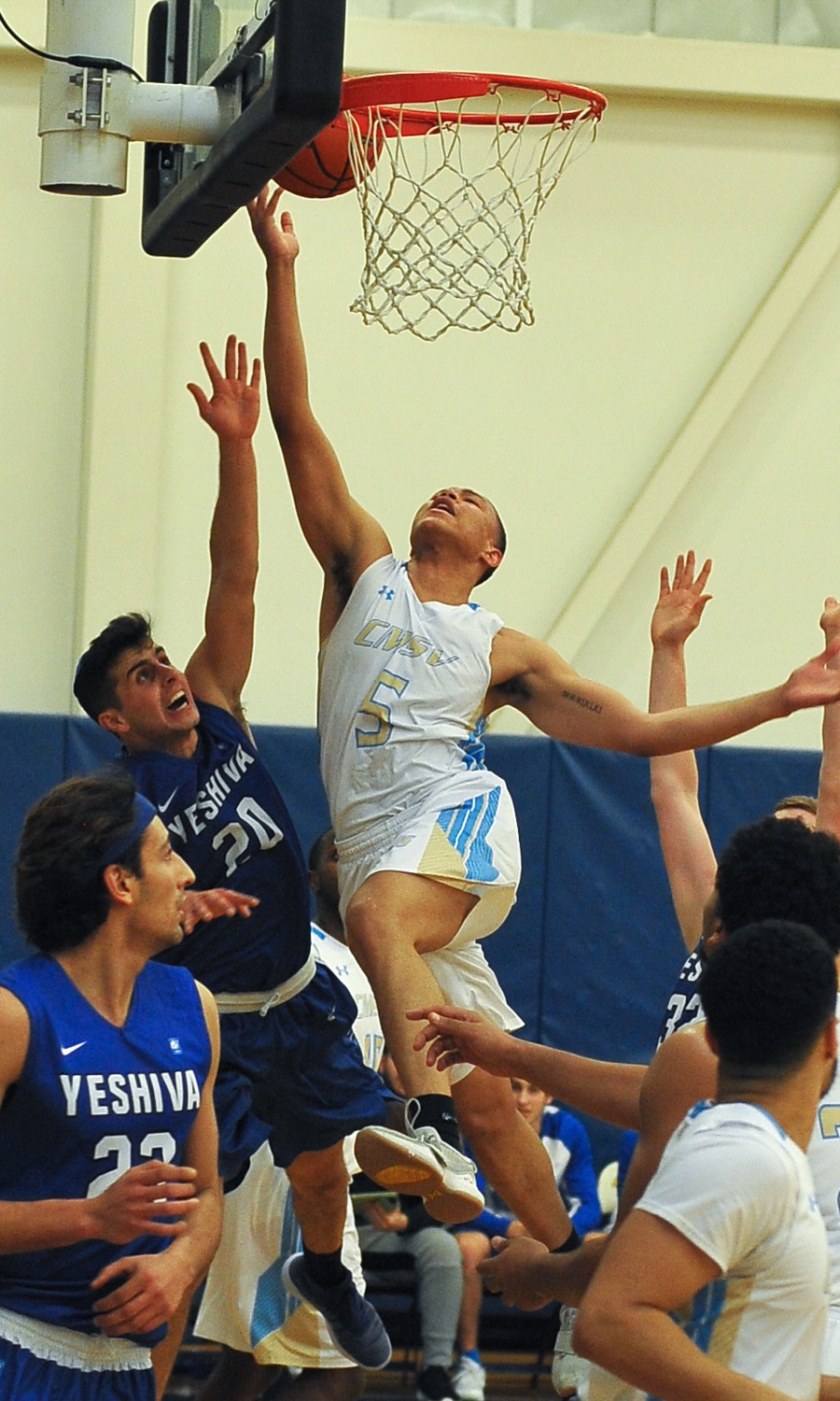 College of Mount Saint Vincent junior guard Jose Barrera slices through Yeshiva defenders to net two of his eight points in The Mount's loss to the Maccabees.