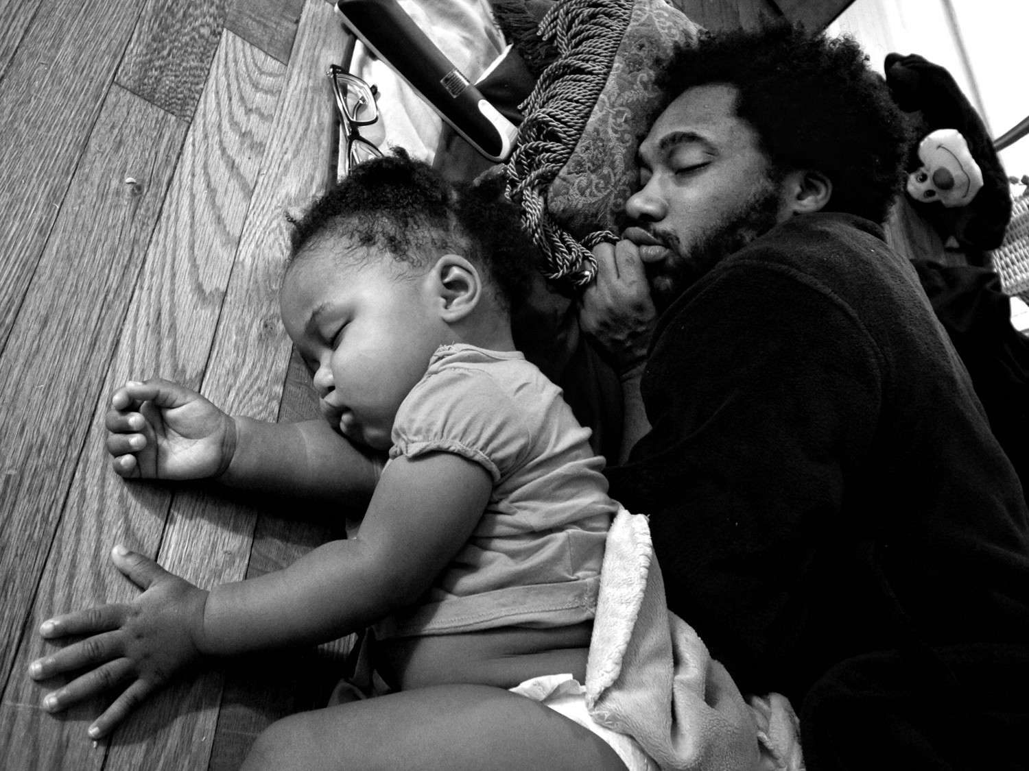 Anthony Francis falls asleep in front of his television with his daughter Tena in Camp Lejeune, North Carolina in 2012. Zun Lee spent three years documenting black fathers and their children in the United States and Canada.