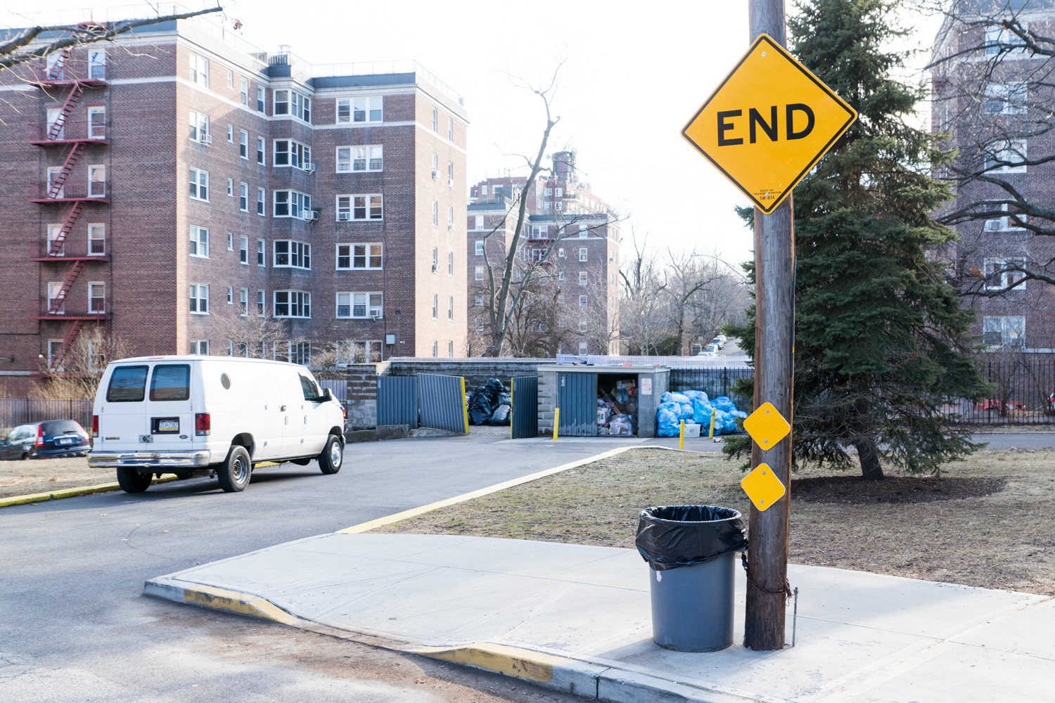 A sign warns pedestrians and motorists of a dead end on Netherland Avenue between West 256th and West 254th streets, where a row of dumpsters and a cinderblock wall blocks access. The North Riverdale Merchants and Business Association is one of the groups pushing to extend sidewalks, creating a connector path that could make it easier for pedestrians.