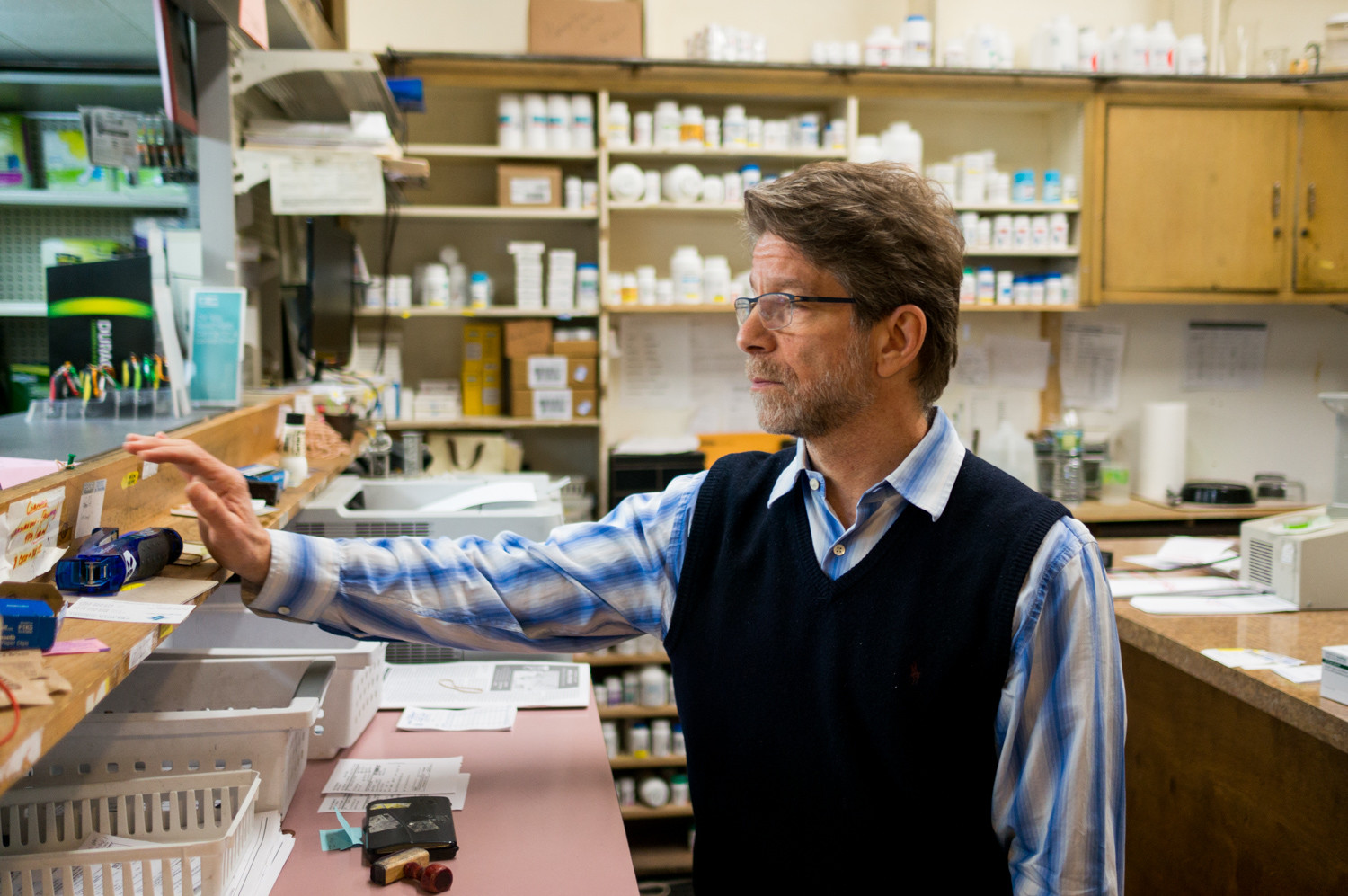 Robert Newman, a pharmacist at Regal Pharmacy, talks with customers. His landline and internet service have been cutting out, which has had a negative impact on business, severely hindering the process of delivering medications to customers. Verizon, he says, has been slow to respond.