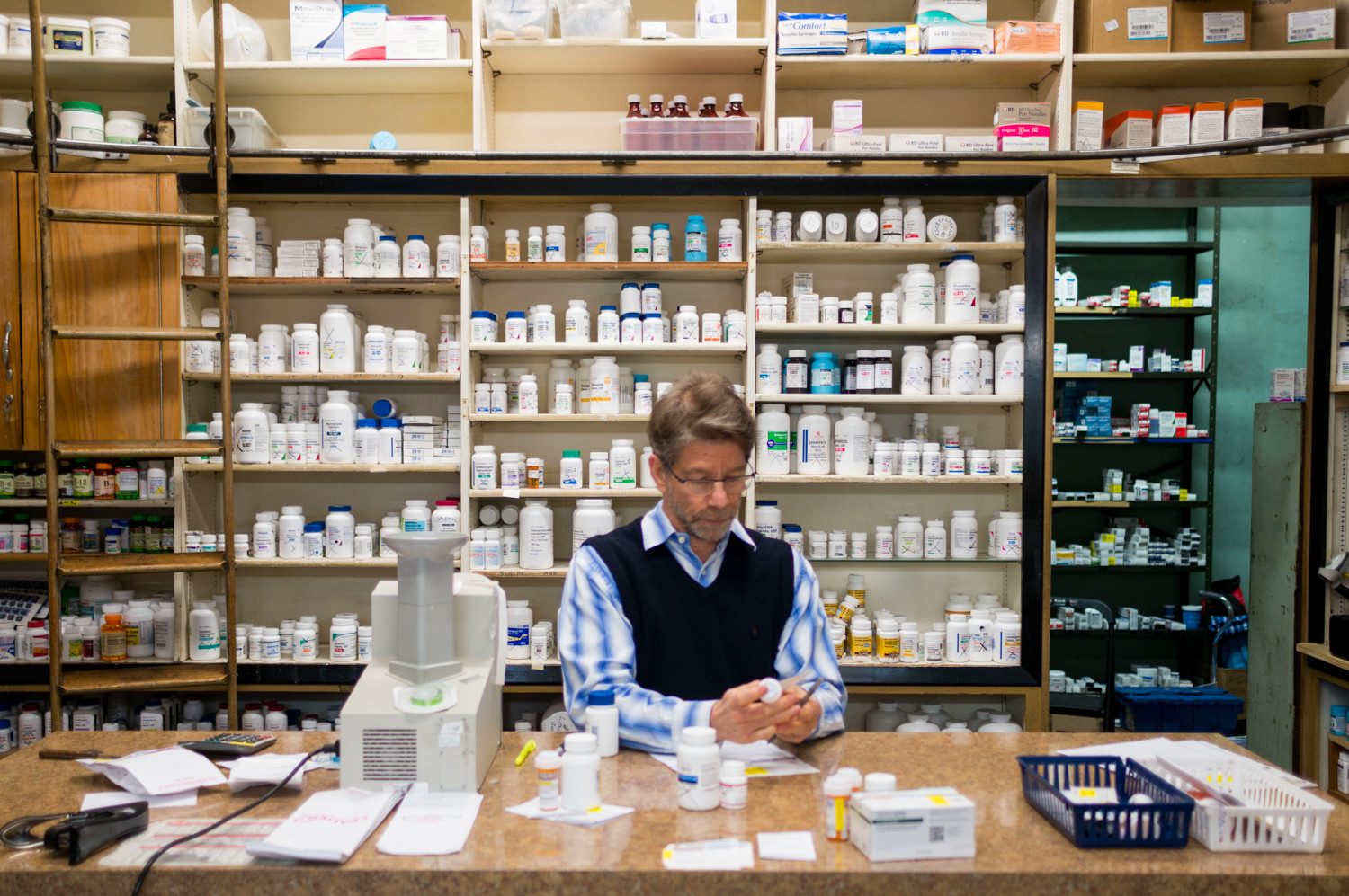 Robert Newman, a pharmacist at Regal Pharmacy, fills a customer's prescription. His internet and telephone service have been cutting out, and Verizon has yet to resolve the problem.