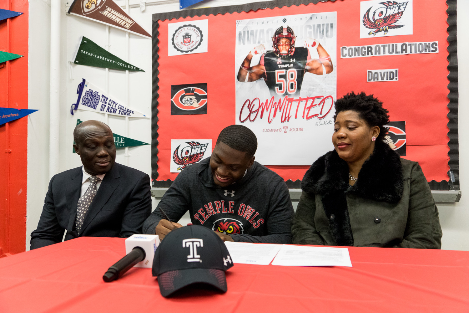 Surrounded by his parents, DeWitt Clinton's David Nwaogwugwu signs his letter of Intent to attend Temple University on a football scholarship.