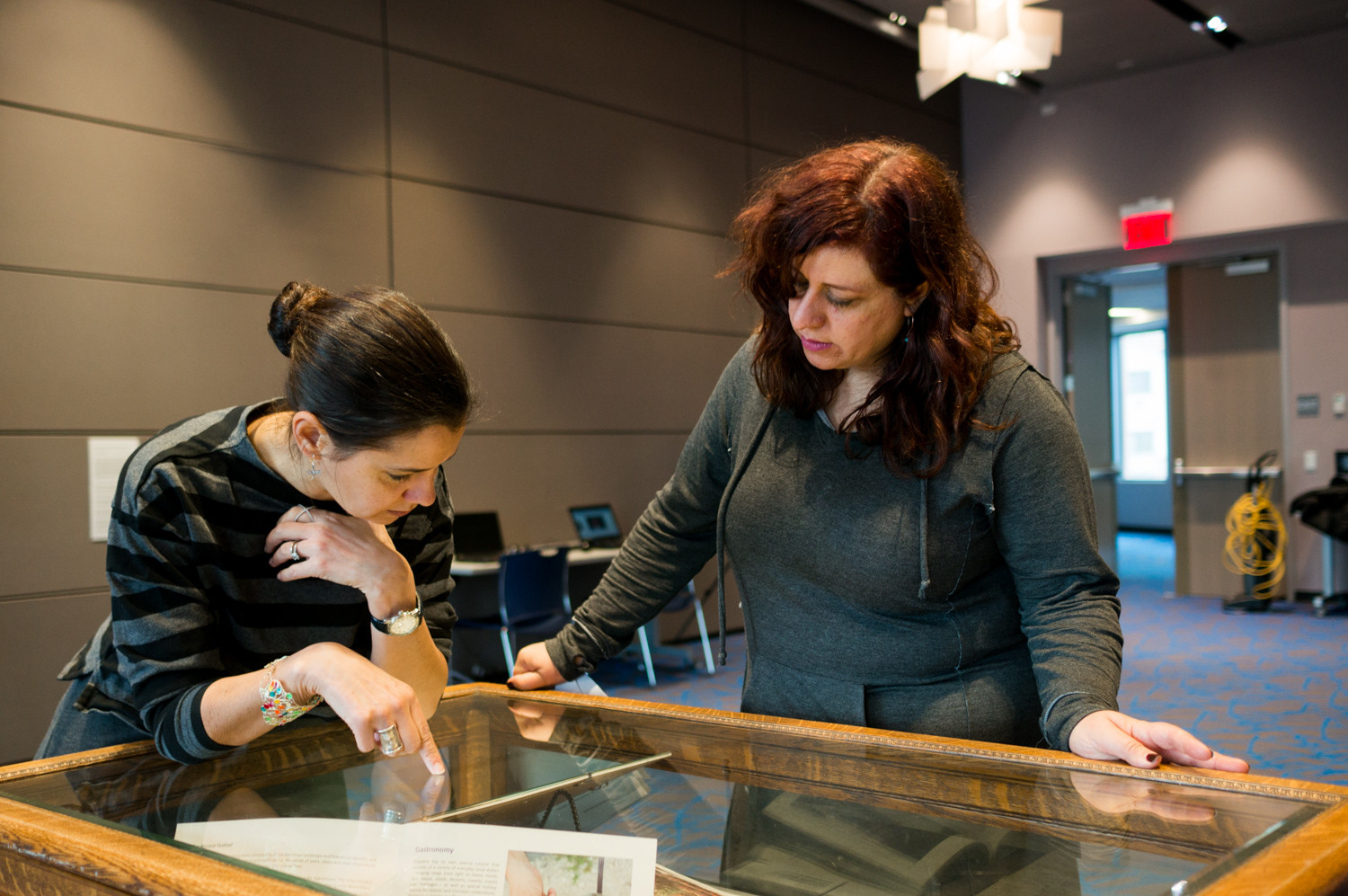 Amy Surak, left, the director of archives and special collections at Manhattan College, and Nada Odeh discuss how to display printed material in a glass case for the exhibition 'Bethlehem Beyond the Wall.' It is on display until Feb. 27.