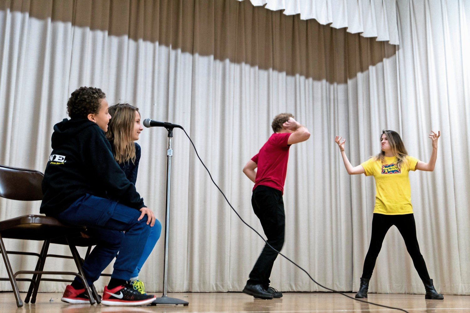 Jacob Chaitkin and Matea Milich provide sound effects for a sketch involving two members of the improv comedy troupe 'Eight is Never Enough' at P.S. 24.