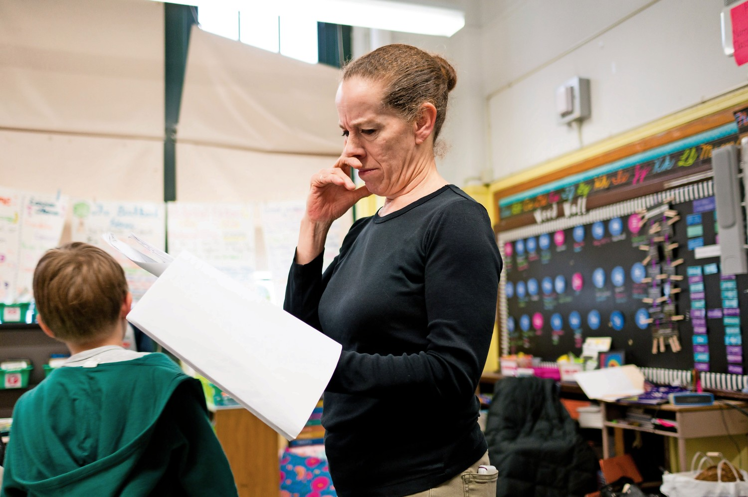 Kim Johnson, an artist in residence at P.S. 81, looks over the script for a play about early American history. All of P.S. 81's fourth grade classes participated in a play portraying early American history. The school has adopted a new social studies curriculum called 'Passport to Social Studies,' which encourages students to think like historians.