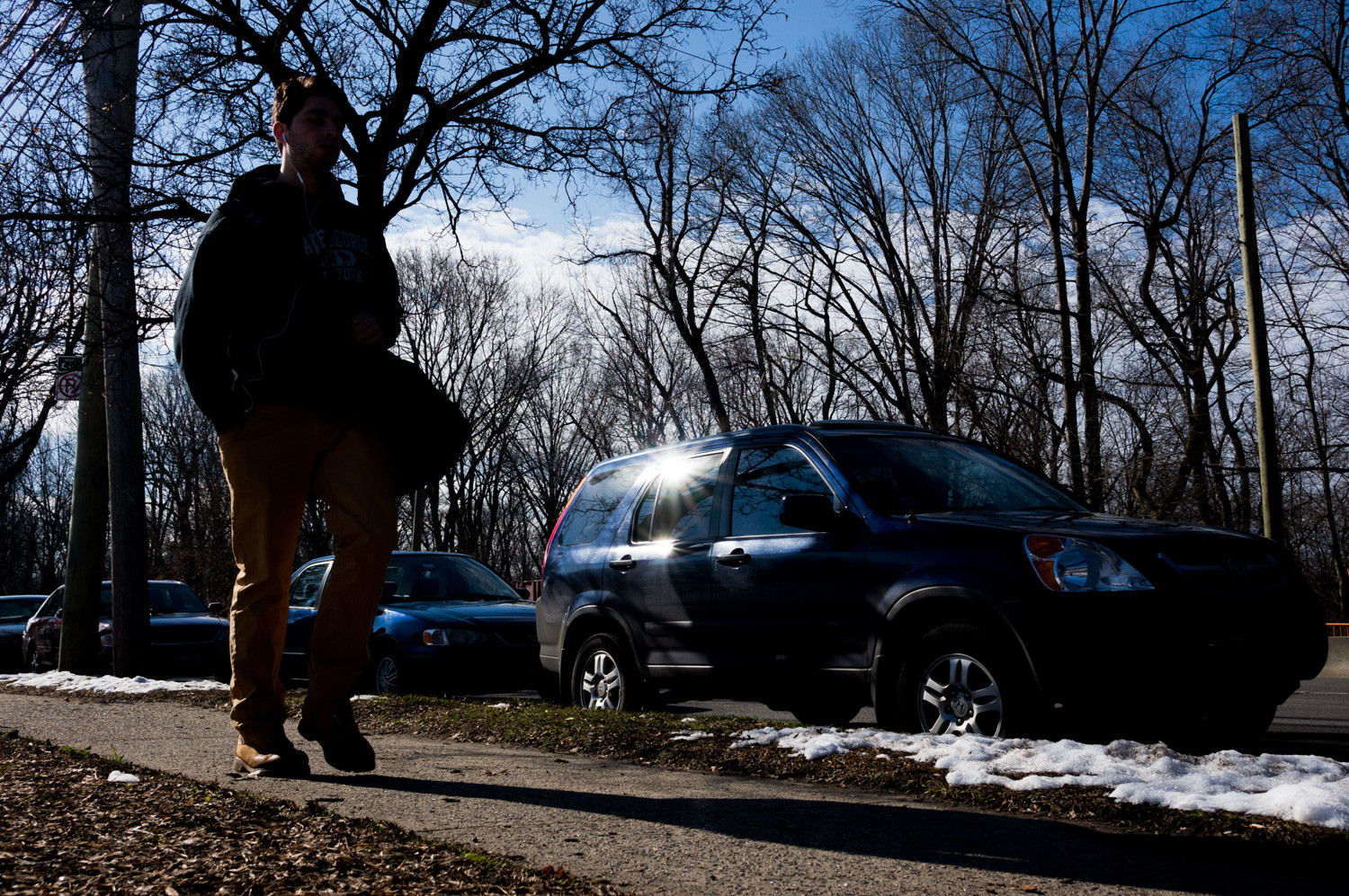A pedestrian walks alongside parked cars on Jerome Avenue near Van Cortlandt Park. A new study by the app SpotAngels found that cars parked along Jerome Avenue near Van Cortlandt Park are particularly susceptible to break-ins.