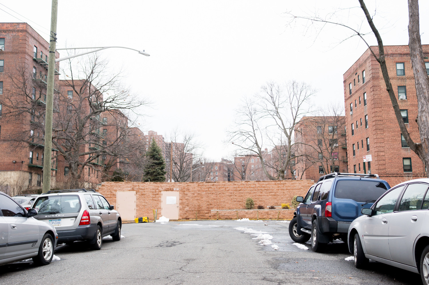 A solid cinder block wall separates two residential complexes on Netherland Avenue between West 254th and West 256th streets. Community Board 8's traffic and transportation committee has rejected an idea to cut a hole through the wall, allowing pedestrians to pass through.