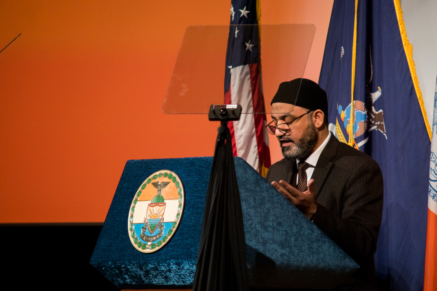 Ali Kamel, an imam at the Muslim American Society's Upper New York subchapter, raises his hands in prayer as he gives the invocation before Ruben Diaz Jr.'s state of the borough address at the Bronx High School of Science.
