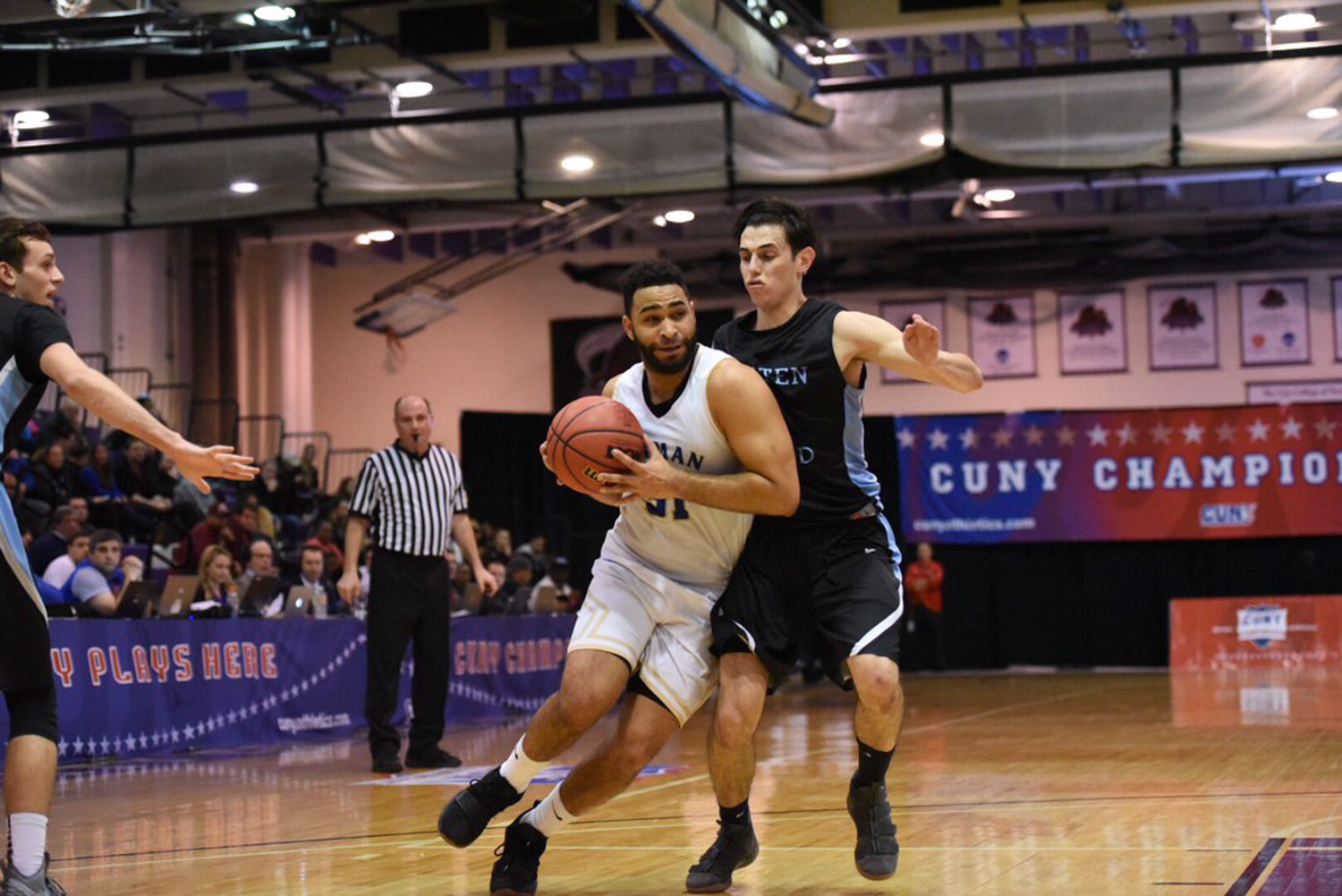 Lehman senior Andrew Utate drives around a Staten Island defender in last Friday's CUNYAC championship game. Utate scored 24 points in a narrow loss to the Dolphins.