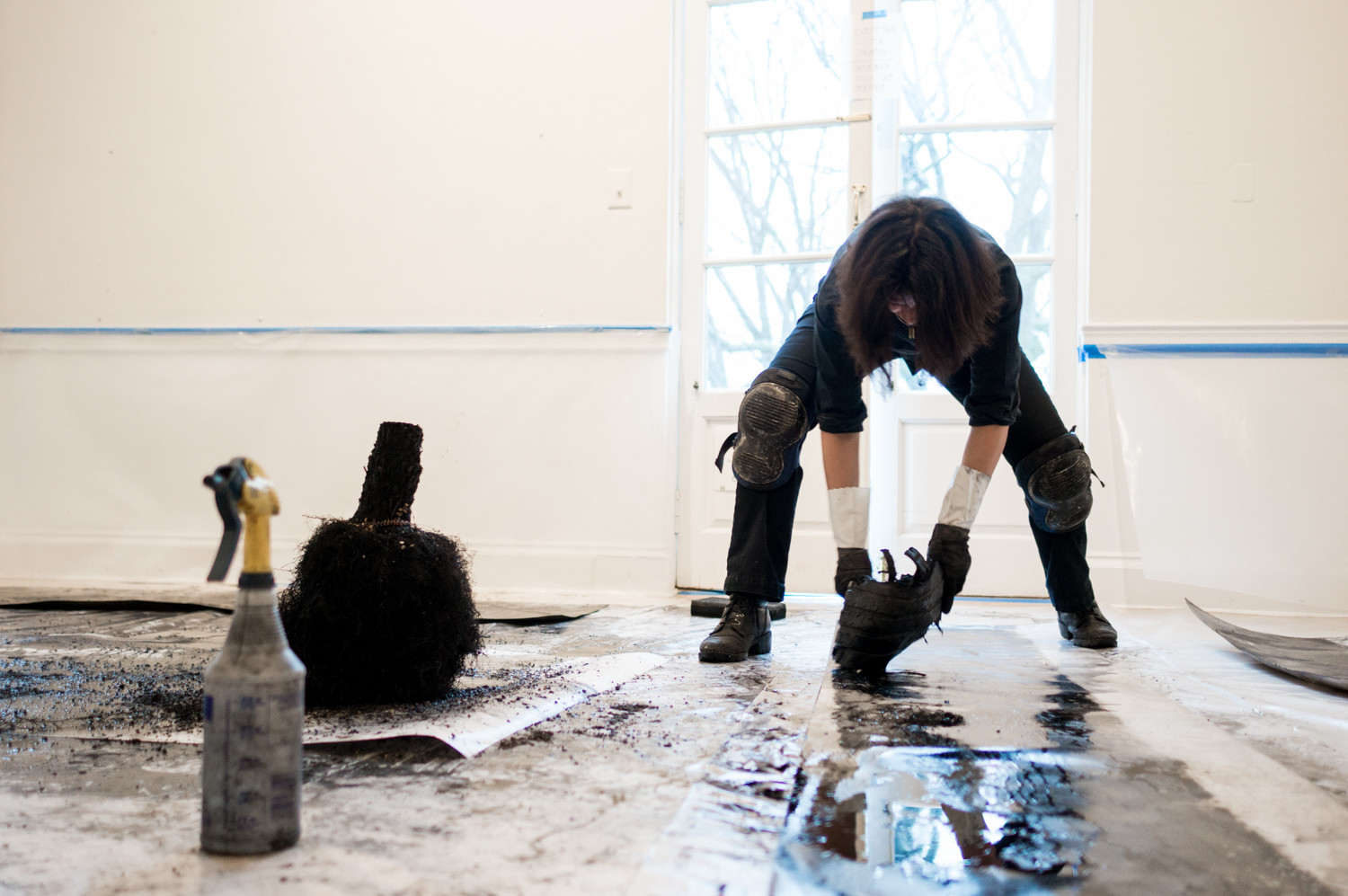 Athena LaTocha uses a tire tread to paint with sumi ink on paper at Wave Hill. LaTocha is an artist in residence at Wave Hill as part of its winter workspace program. LaTocha uses found materials like sumi ink — made from the soot of pine branches in Japan — to make her paintings.