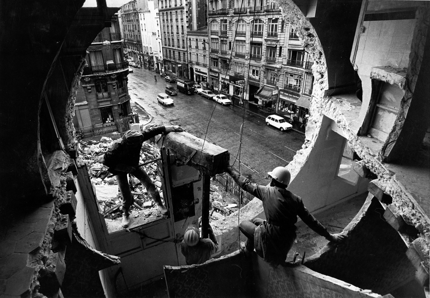 Gordon Matta-Clark, with crowbar at left, works with Gerry Hovagimyan on 'Conical Intersect' in 1975. In this piece, which turns an abandoned Parisian building into sculpture on a giant scale, Matta-Clark provides commentary about how the idea of social stratification makes inequalities like income, race and education more apparent in society.