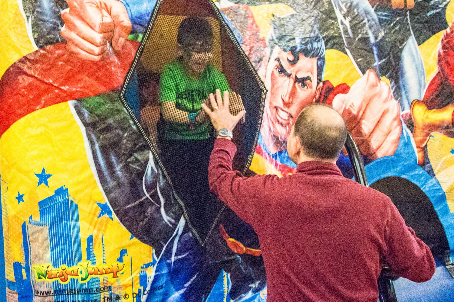 A father high-fives his son through the mesh windows of a Justice League-themed inflatable bounce house during Riverdale Temple's Purim carnival.