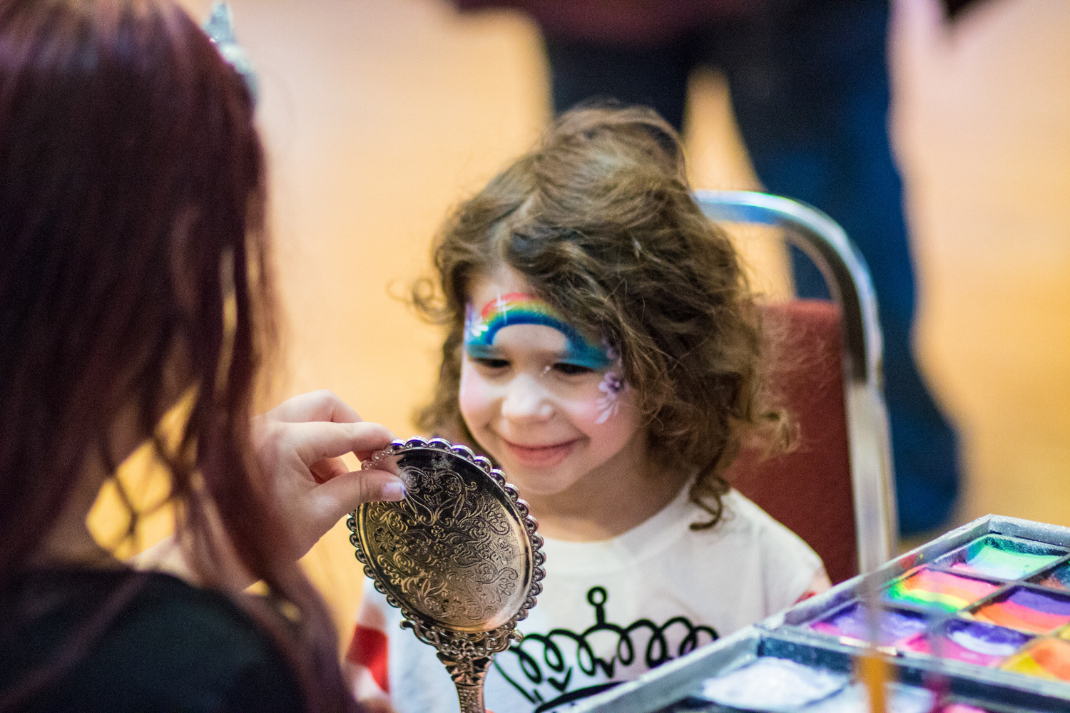 After getting a rainbow painted on her face at the carnival, a young girl smiles at her reflection in a small handheld mirror.
